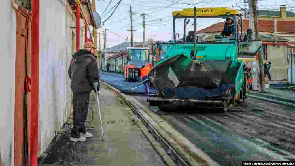 Житель сусіднього будинку спостерігає за ремонтом дороги на вулиці Чехова