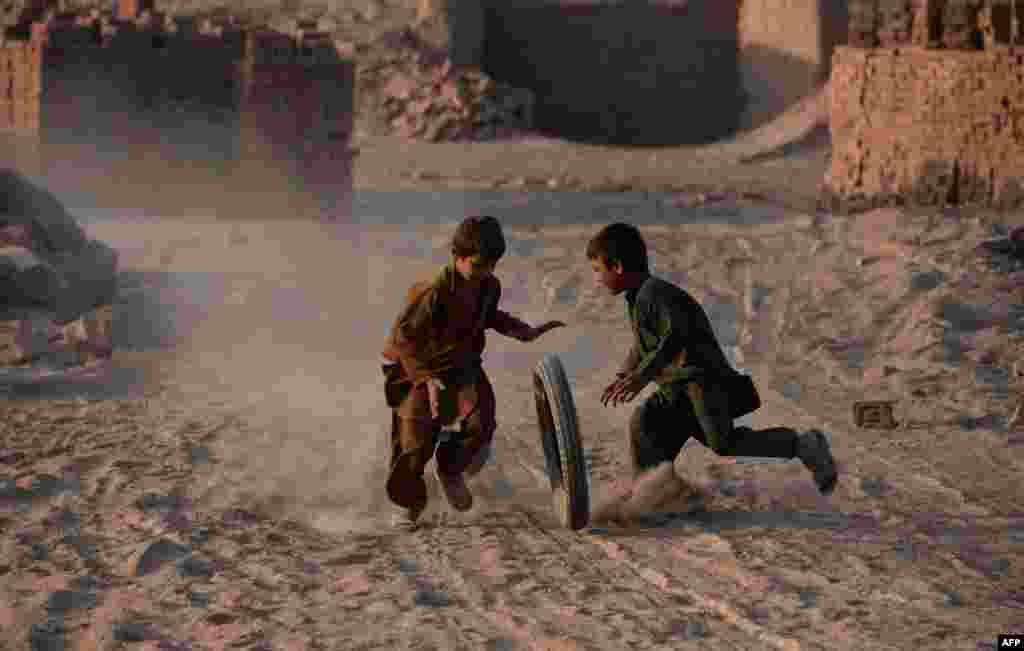 Afghan children play with a tire along a dusty road on the outskirts of Jalalabad. (AFP/Noorullah Shirzada)