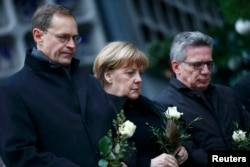 Berlin Mayor Michael Mueller (left), German Chancellor Angela Merkel (center), and German Interior Minister Thomas de Maiziere stand in silence at the site of the attack in Berlin on December 20.