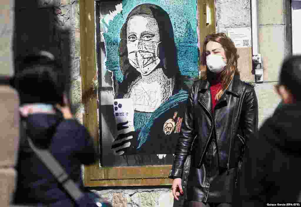 A tourist in Barcelona, Spain, poses for a souvenir photo next to graffiti showing the Mona Lisa wearing a mask, titled Mobile World Virus.