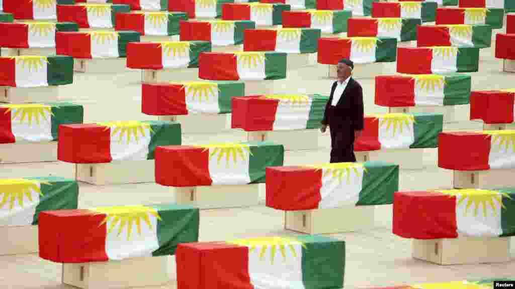 Курд проходит между гробами с останками более 700 курдов - жертв режима Саддама Хусейна - во время церемонии перезахоронения в Сулеймании, в 260 километрах от Багдада, 28 мая. По данным правозащитных организаций, около 180 тысяч курдов погибли в результате операции, которую режим Саддама Хусейна начал в 1988 году. (Reuters)
