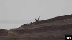 An Islamic State militant waves his hands and gun from a hill near Kobani, in Syria. (file photo)
