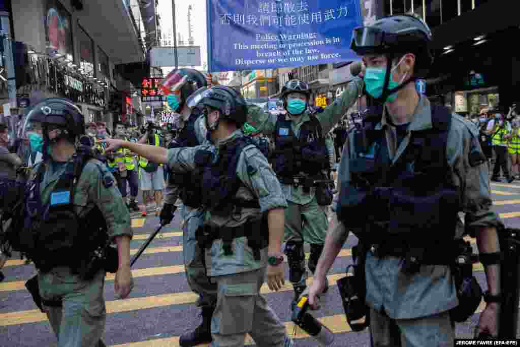 Police clear a street during a silent march against the national security law in Hong Kong, June 28, 2020.
