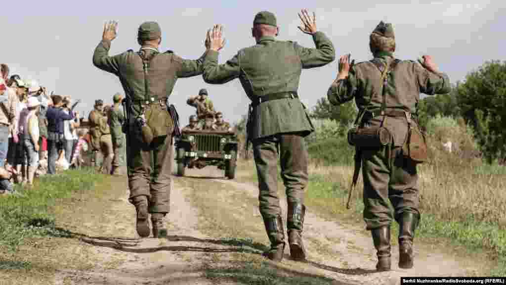 Реконструкція бою 1945-го року між військами союзників і Вермахтом. Троє німецьких солдат йдуть здаватись в полон армії союзників