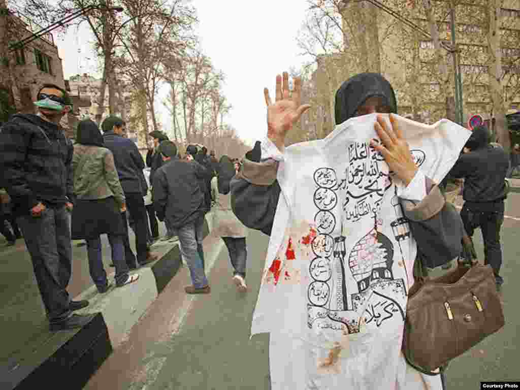 Iran -- An Iranian woman mask her face with a Ashura slogan (blood smear) during anti-government demonstration in Tehran, 27Dec2009 - Photo by Dara (Use only with Photographer's name