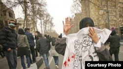 An Iranian woman masks her face with an Ashura slogan during an antigovernment demonstration in Tehran on December 27.