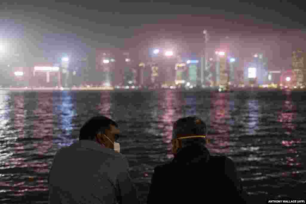 Two men wearing face masks as a precautionary measure against the coronavirus chat while standing near Victoria Harbour in Hong Kong on March 13. (AFP/Anthony Wallace)