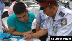 Полицейский составляет протокол о нарушении на капоте автомобиля.