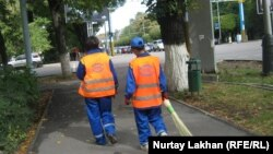 Дворники идут по тротуару. Алматы, 23 сентяюря 2011 года. Иллюстративное фото.