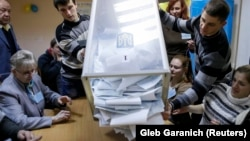Ukraine -- Members of a local electoral commission empty a ballot box at a polling station after voting day in Kiev, October 26, 2014.