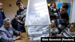 Члены местной избирательной комиссии вываливают на стол бюллетени из урны для голосования. Киев, 26 октября 2014 года.