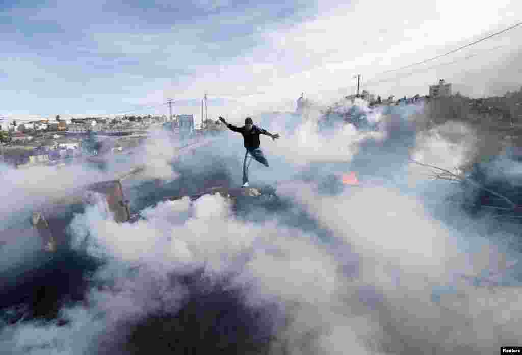 A Palestinian protester jumps as tear gas fired by Israeli soldiers rises during clashes in Jalazoun refugee camp near the West Bank city of Ramallah on January 31. (Reuters/Mohamad Torokma)