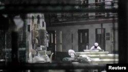 Заключенный лагеря № 6 тюрьмы Гуантанамо читает газету. 5 марта 2013 года.