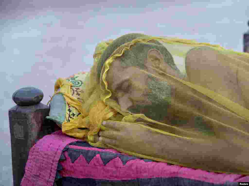 A man, displaced by heavy floods for almost a year, sleeps with his face covered with a net to avoid insects while taking refuge in a camp for flood victims in Pakistan's Sindh Province.Photo by Akhtar Soomro for Reuters