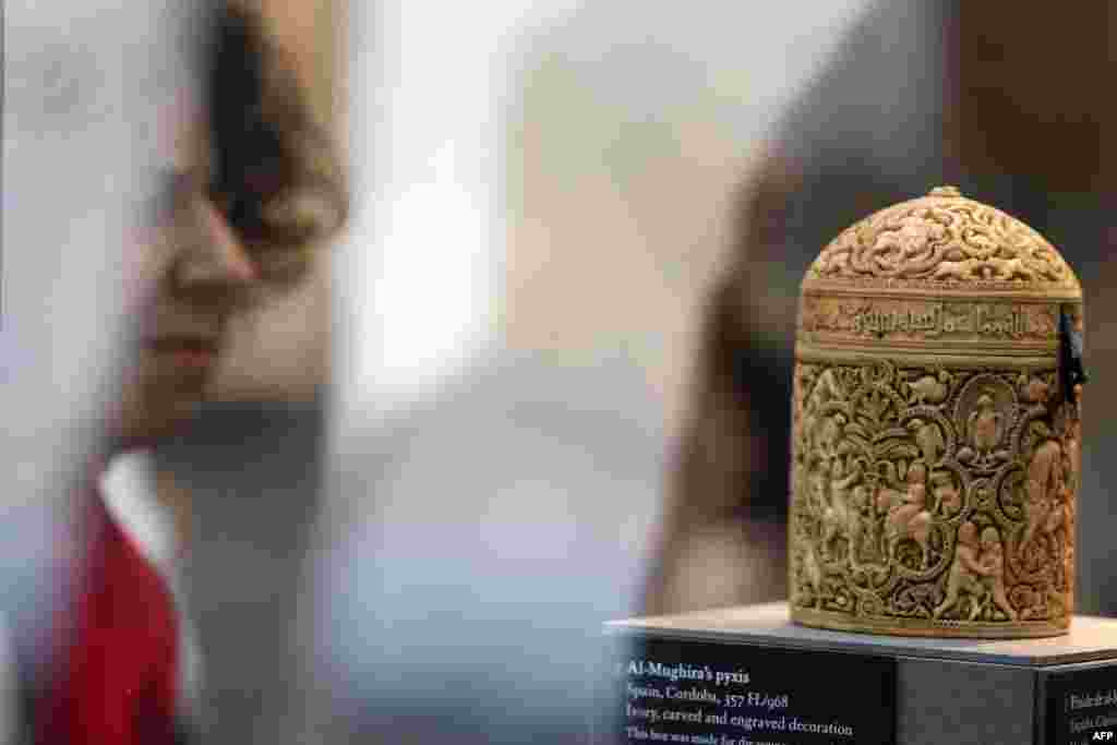 "A woman examines a box called ""Al-Mughira's Pyxis"" on a visit to the new Islamic Arts Department at the Louvre."