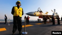 "Chinese servicemen check a J-15 fighter jet on the Chinese aircraft carrier ""Liaoning."" (undated)"