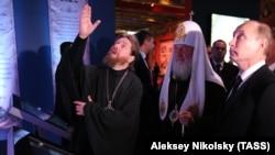Archimandrite Tikhon (left), who has been described as Putin's spiritual mentor, took the exhibition under his wing.