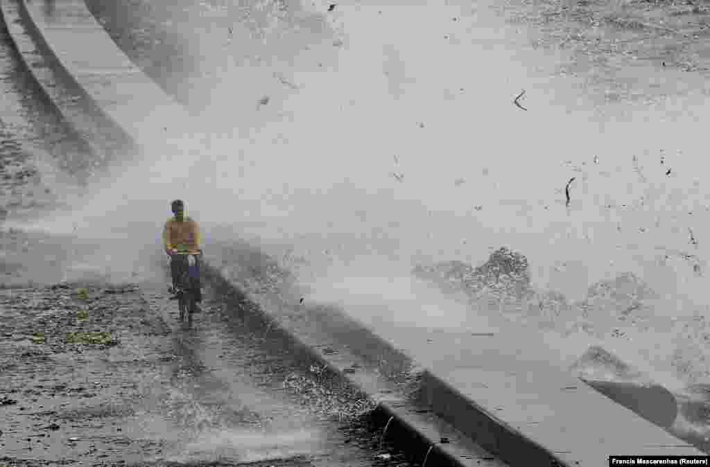 A man rides his bicycle as a wave crashes during high tide at a sea front in Mumbai, India. (Reuters/Francis Mascarenhas)