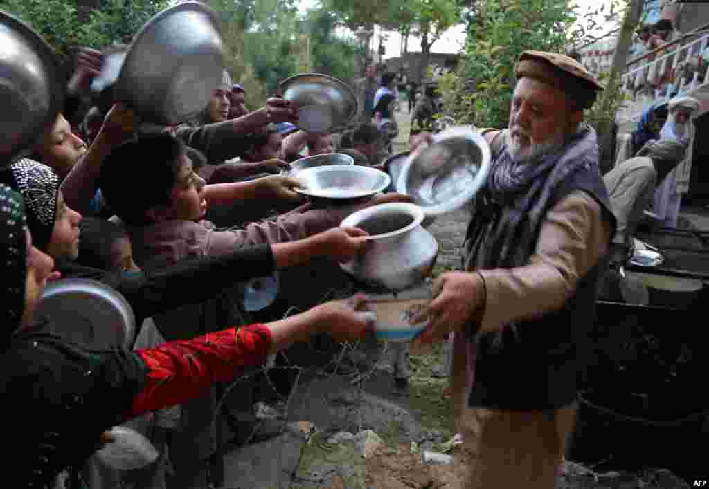 An Afghan man distributes food for the needy during the first day of the Islamic holy month of Ramadan in Ghazni Province on June 6. (AFP/Zakeria Hashimi)