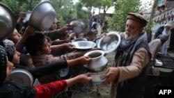 آرشیف، یک مرد افغان در حال توزیع مواد غذایی در ولایت غزنی افغانستان