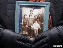 Женщина держит фотографию своей семьи во время памятных мероприятий в Киеве – 26 ноября 2011 года
