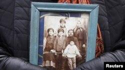 Жінка тримає світлину своїх рідних на вшануванні пам'яті жертв Голодомору 1932–1933 років та сталінських репресій проти селянства