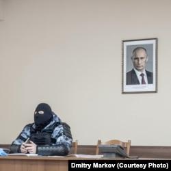 Ыстық бөлмеде бетін тұмшалап, балаклава киіп отырған полицей. Жоғарыда - Ресей президенті Владимир Путиннің портреті.