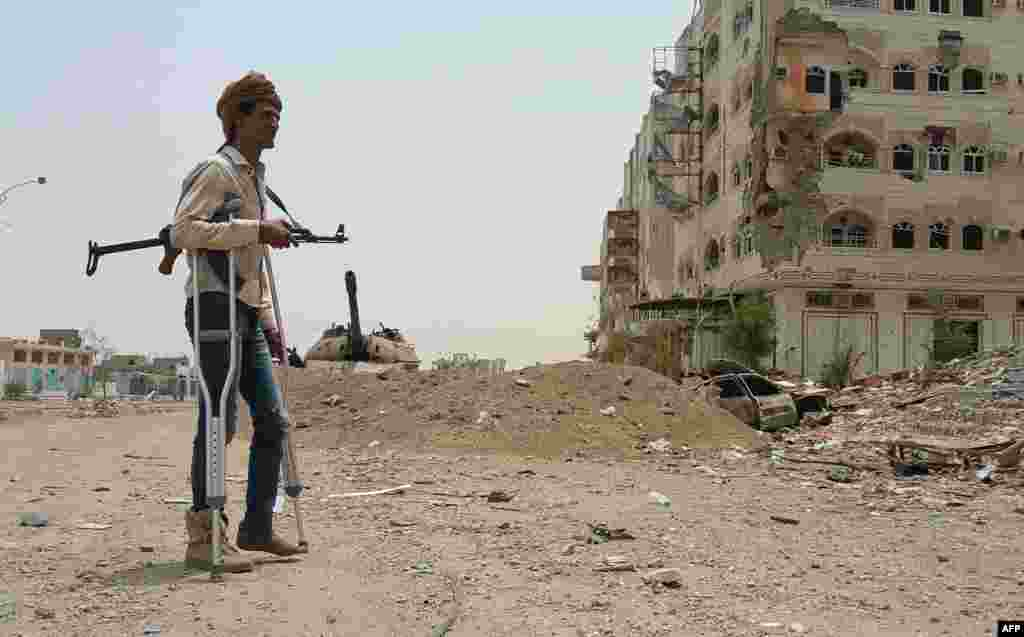 A fighter loyal to Yemen's exiled President Abedrabbo Mansour Hadi walks with crutches in Aden on July 30. (AFP)