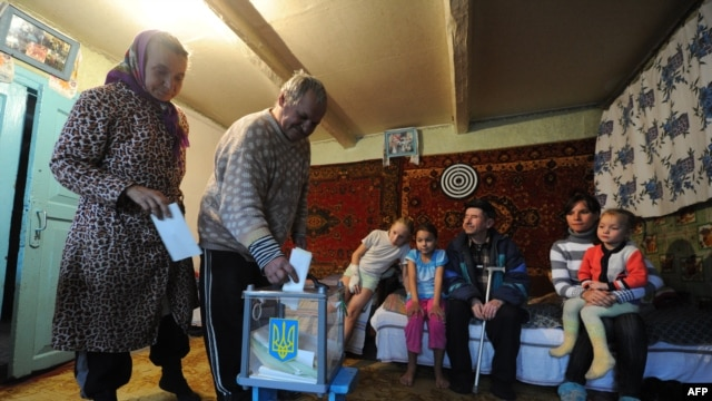 An elderly couple casts their ballots in the village of Rusaki in Ukraine's national elections for a new parliament on October 28.