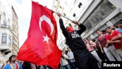 A masked demonstrator waves a Turkish flag during a protest in central Istanbul in late May.