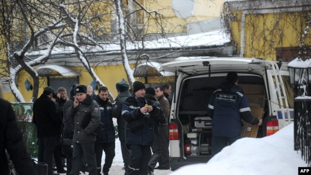 "Russian police officers and investigators crowd at the site of the killing of Aslan Usoyan, better known as ""Ded Khasan"" (Grandfather Khasan), outside the Karetny Dvor restaurant in central Moscow in mid-January."