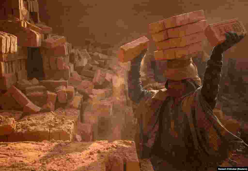 A worker stack bricks on his head at a factory in Bhaktapur, Nepal. (Reuters/Navesh Chitrakar)