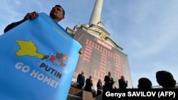 "A man holds sign that reads ""Putin go home"" during a memorial ceremony in commemoration of the 75th anniversary of the deportation of the indigenous population of the Crimea by the Soviet Union in Kyiv on May 18."