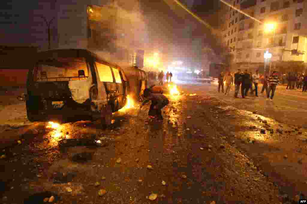 Egyptian demonstrators fuel the fire next to burning police vehicles in Cairo.