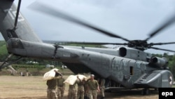 Pakistani soldiers load food supplies for stranded flood victims onto a U.S. Navy helicopter for distribution in August 2010.
