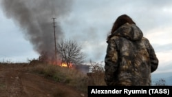 A local resident looks at a burning house in the town of Lachin (Berdzor), November 30, 2020.
