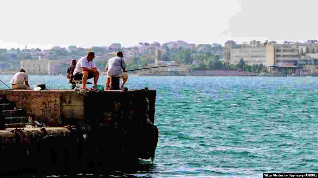 Рыбаки на причале в ожидании улова
