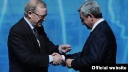 Франция – Председатель Европейской народной партии Вилфрид Мартенс (слева) вручает значок партии президенту Армении Сержу Саргсяну, 8 декабря 2011 г.