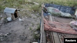 A migrant worker sleeps on top of a shelter outside Moscow.