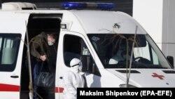 Специалист в защитном костюме сопровождает пациента в многопрофильный больничный комплекс в поселке Коммунарка, Москва, 26 марта 2020 г.