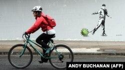 Biciklista prolazi pored grafita u Glazgovu koji je inspirisan pandemijom korona virusa