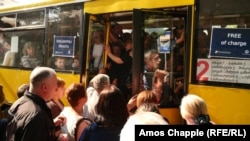 "Crammed buses with signs reading ""FREE of charge"" continue to ferry commuters throughout Tbilisi on June 5."