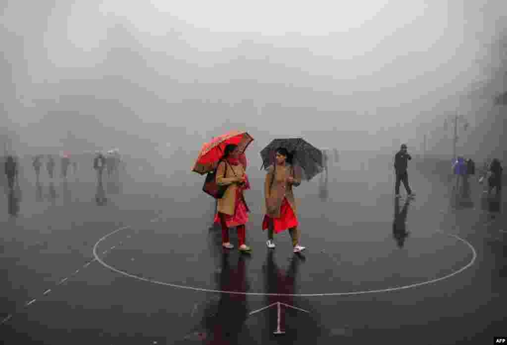 Indian women carry umbrellas as they walk during a rainfall in the northern hill town of Shimla. (AFP/Stringer)