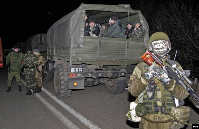 Ukrainian prisoners of war sit in a truck during their transportation to a place of exchange for pro-Russian rebels on December 26.