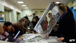 Members of a local electoral commission count ballots at a polling station in Kiev.