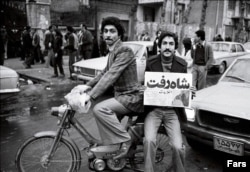 """A man waves a newspaper announcing """"The Shah Left"""" during demonstrations in Tehran in 1979."""
