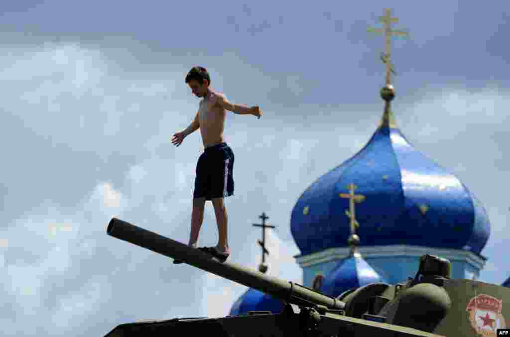 A boy plays on an armored personnel carrier mounted on a plinth in the village of Chernitsyno, in Russia's Kursk region. (AFP/Sergei Gapon)