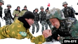 Chinese and Tajik soldiers arm wrestle during patrols near the city of Kashgar, in the northwestern autonomous region of Xinjiang, in May 2019.