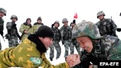Китайские и таджикские солдаты мерятся силой во время патрулирования рядом с городом Кашгар в автономной области Синьцзян, Китай. Май 2019 года.