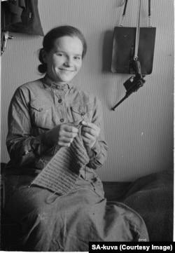 Фінська жінка з пістолетом на стіні своєї садиби. Війна стала для фінів кризою, яка об'єднала людей. Бойовий дух захисників був на високому рівні